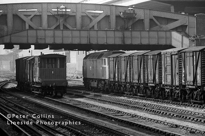 In the mid-1970s, a Class 47 Brush Type 4 (D1637) makes up its train of fitted vans in the yard adjacent to Royal Oak underground station on the Hammersmith branch near London Paddington station.