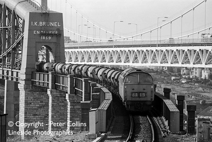 A crisp spring Sunday in 1973 sees a Western Class 52 diesel hydraulic idle off Brunel's superb Saltash bridge as it heads the daily Penzance to Kensington milk train out of Cornwall into Devon and along the sinuous section of the GWR on the way to Plymouth and beyond.