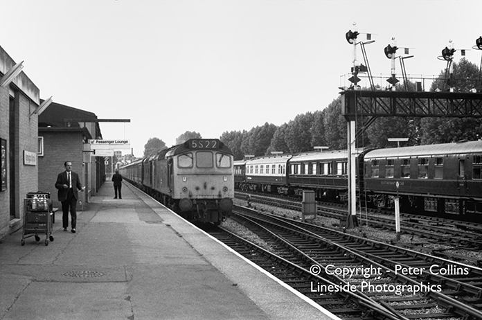 Due to extensive engineering works outside Euston station one Sunday in the 1970s, many long-distance West Coast trains started and terminated at Kensington Olympia and here a set of empty stock to form a Scottish service is brought into one of the West London platforms by double-headed Sulzer Type 2 Class 25s. On the adjacent platform stands the empty stock of the Royal Train which then consisted of some pre-grouping vehicles as well as Mark 1 coaches.