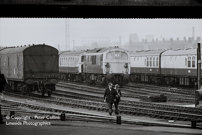 Class 74 E6007 awaits its next duty at Clapham Carriage Sidings sometime in the early 1970s. Two Ladies walk back towards Clapham Junction station deep in conversation, but who are they?