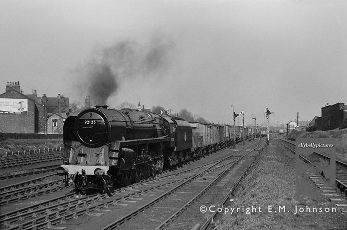 Brand New BR Standard 9F 92125 is seen on a running-in turn somewhere in the Stockport area on possibly 21st March 1957. Can you help with the location and date?